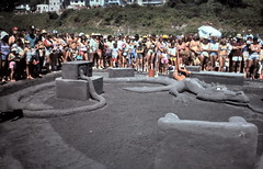 gm_10336 Beach Sandcastle Contest Dragon, White Rock, BC 1984 (CanadaGood) Tags: bc britishcolumbia whiterock sea analog beach sandcastlecontest 1984 slidefilm kodachrome slidecube green colour color person people canadagood canada eighties semiahmoobay shore
