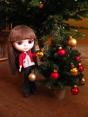 Decorating her tree with gold balls