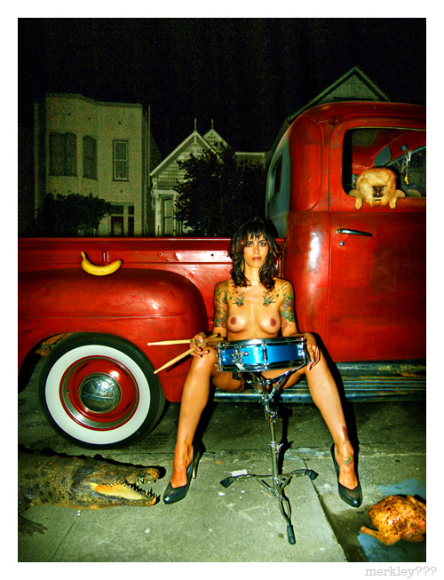 Julianna - Poses With Her Blue Snare & Drum Sticks Seated On a Red 1950 Ford Truck While a Fuzz Head Window Monkey & Open Jawed Sidewalk Crocodile Eyeball a Baked Chicken as a Perfect Banana Goes Unnoticed on The Fender