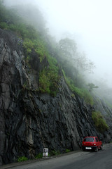misty mountains (vbsuresh) Tags: road trees red india black mountains wet car rock misty fog contrast kerala hills greens fade milestone wayanad rains maruti 40d