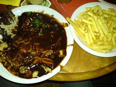 Schnitzel med pommes frites og sovsbacon, svampe, løg og pommes frite