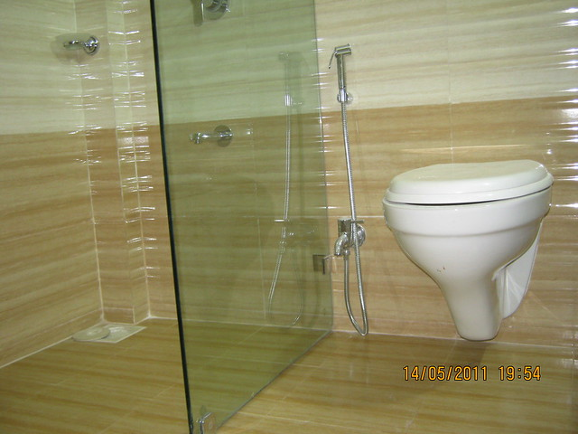 Glass partition, wall hung European commode, chrome plated (Jaguar / equivalent) fittings), anti-skid flooring in a  2 BHK Sample Flat in Om Developers' Tropica, Blessed Township at Ravet PCMC, Pune 412 101