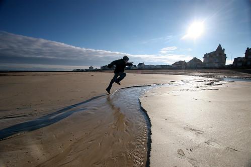 Un enfant saute au dessus d'un ruisseau, sur une plage