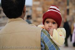 Here's Looking At You, Kid (Richard Buttrey) Tags: baby india brick hat 50mm nikon minaret delhi nikkor qutub minar qutubminar lightroom d300