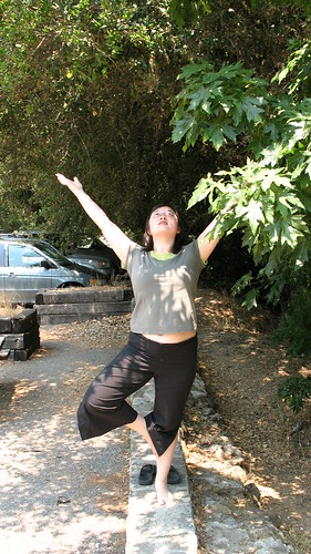 Lisa doing tree pose under a tree