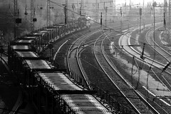 Rail tracks and freight train  Marzahn, Berlin (Ole Begemann) Tags: city railroad light bw berlin lines germany deutschland licht vanishingpoint blackwhite europa europe industrial traffic geometry curves cityscapes eisenbahn railway zug trains cables stadt rails maze sw 2008 verkehr labyrinth backlighting kabel gegenlicht tangled catenary strommasten leitungen oberleitung stadtbild freighttrain geometrie railwaytracks zge schienen alleederkosmonauten marzahn springpfuhl gterzug linien powerpoles kurven schwarzweis overheadline fluchtpunkt camera:iso=200 verheddert camera:model=canoneos20d camera:shutter=sec lens:focallength=200mm lens:aperture=f11 signalmasten signalposts original:filename=2008110120d037059