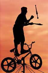 Busker on tightrope with bicycle silhouette