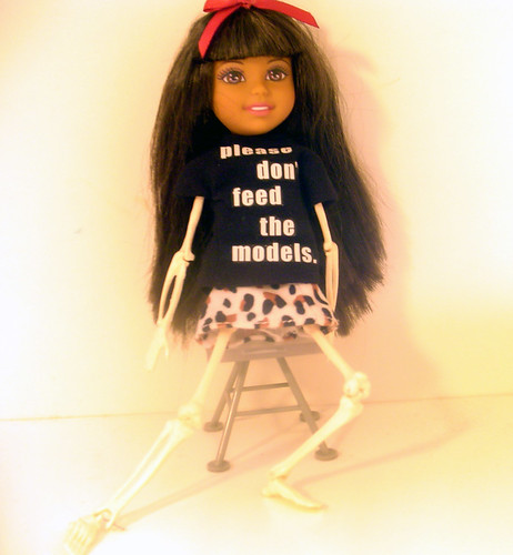 "The Doll Project: ""Please Don't Feed The Models"" Skeleton Ana wears a t-shirt proclaiming her refusal to eat"