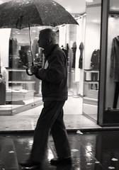 old man in the rain (clickykbd) Tags: nov street old travel bw italy man rome roma window rain umbrella canon person mono store italia candid clickykbd lazio 2007 bwconverted sd1000 sopahide
