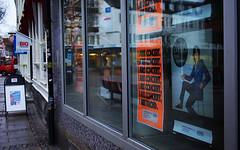 Poster reflection (wristoarwatch) Tags: street orange macro reflection window glass shop cs2 pentax da posters 35 limited f28 k10d wristoarwatch