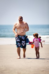 Dad and daughter walking on beach (Rebecca812) Tags: ocean family vacation sky orange man love beach sunglasses walking togetherness kid bucket sand dad waves child husband parent onthemove bonding pail beachscene sunhat daugter swimmingsuits canon5dmarkii rebecca812 heritage2011