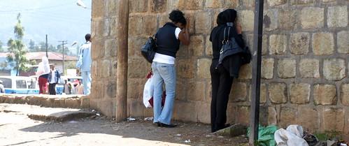 Mujeres orando en el muro exterior de una iglesia