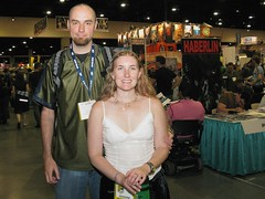 Hey... what do you know?  A picture of both Sarah and I at Comic Con. (colorblindPICASO) Tags: california travel smiling sarah goatee arms watch longhair jeans comiccon blackdress whitetop blondhair hairdown bareshoulders blackskirt sandiegocomiccon silvernecklace whitetanktop postertube skirtblack comiccon2008 sdcc2008 shirtshaved skirtmesarahboth usgreen headbackpackbatman