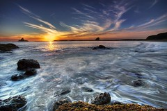 Swirls of life (Mark Emirali) Tags: ocean sunset sea newzealand sky sun seascape motion blur colour art clouds canon landscape rocks searchthebest nz swirl aotearoa 1022mm 30d copyrighted whatipu canon30d pleasedonotusewithoutmypermission impressedbeauty travelplanet maloe4 maloephoto maloephotography markemirali markemiraliphotography
