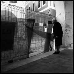 Curioseando (joanpetrus) Tags: street blackandwhite bw woman square mujer strada noiretblanc preto explore squareformat bianco blanc nero negre menorca biancoenero dona blancinegre 500x500 bsquare bwdreams 123bw monochromia incoloro ofstreet joanpetrus stphotographia