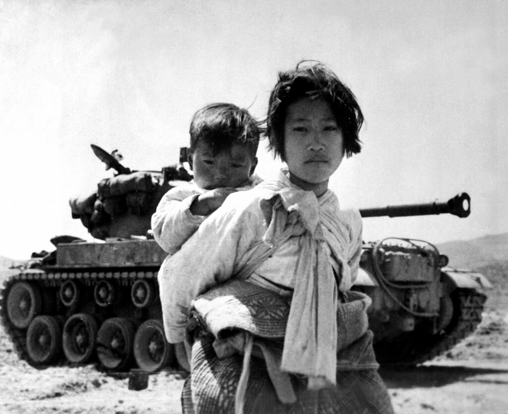 With her brother on her back a war weary Korean girl tiredly...
