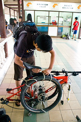 David tieing and packing up his bike (Y-Shumin) Tags: bike bicycle train cycling nikon singapore long packing tie luggage malaysia distance 18200 touring compact improvise d40 sgima