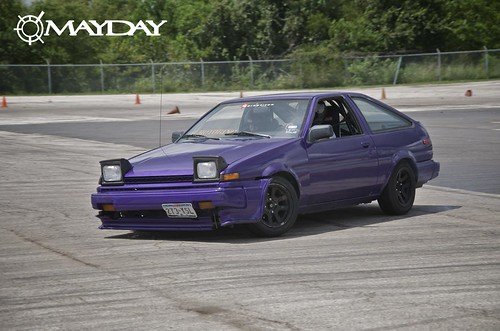 A purple AE86 dipping into turn one