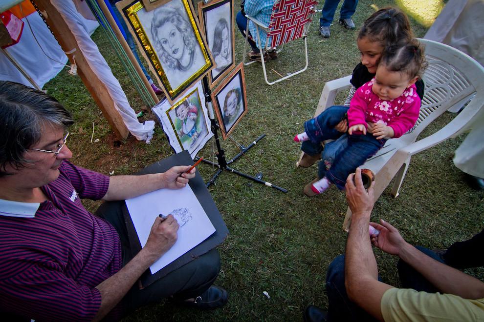 En la Plaza de San Miguel y en medio de las celebraciones de la tradicional festividad del Ovecha Rague, existían diversos stands que ofrecían al público todo tipo de atracciones, como este retratista que dibujaba a mano alzada. (Tetsu Espósito, San Miguel - Paraguay)