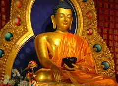 Statue of Lord Buddha in the Bhumisparsha - Earth Touching Mudra, Tsog Kor evening, Tibetan Buddhism, Seattle, Washington, USA (Wonderlane) Tags: seattle flowers orange usa beautiful person gold golden photo washington shrine colorful peace image buddhist silk halo happiness teacher clear holy master mind formalwear creativecommons meditation lovely jewels enlightenment aura shrineroom 2909 guru buddhas garment mudra bhumisparsha wonderlane beggingbowl statueofbuddha tsog earthtouchingmudra callingtheearthtowitness statueoflordbuddha endofsuffering tsogkorevening victoryovermara beautifulbuddha