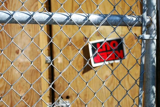 Image of a Keep Out sign behind a fence