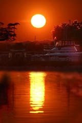 csi: liverpool (chromatophobe) Tags: trees sunset orange sun lake newyork reflection tree water silhouette clouds boat haze glare onondagalake sunhalo