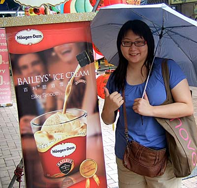 Suanie next to a Baileys Haagen Dazs sign in Stanley Market, Hong Kong