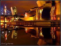 Guggenheim Bilbao Design and Color of Frank Gehry's at Night (david gutierrez [ www.davidgutierrez.co.uk ]) Tags: city bridge light red urban color colour reflection building colors museum architecture modern night buildings river dark spectacular frank stars geotagged photography design interestingness spain arquitectura europe cityscape colours shadows darkness dusk centre shapes cities gehry center front structure architectural bilbao explore espana nighttime finepix page architektur nights fujifilm sensational guggenheim metropolis topf100 frontpage frankgehry bizkaia impressive basquecountry nightfall municipality edifice gehrys 100faves s6500fd s6000fd fujifilmfinepixs6500fd frankgehrys gehrysdesignandcolors frankgehrysdesignandcolors designandcolors