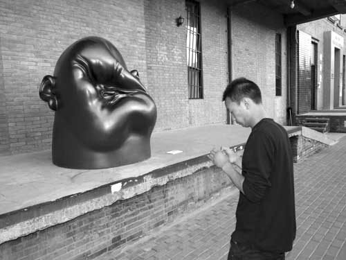 A visitor to the 798 art district looks at his photos, while a crushed face looks at him.