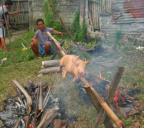 Philippines,Pinoy,Filipino,Pilipino,Buhay,Life,people,pictures,photos,city,rural,scene, man, traditional, sitting cooking pig roasting lechon