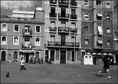 Two children and a pidgeon. (flevia) Tags: barcelona bw film blackwhite spain barca bcn bn espana ilfordhp5 pelicula barrio barcellona biancoenero spagna nikonfa analogic labarceloneta pellicola epsonscanner castigliano scannednegatives epsonv700 bnarchitettura bncitt ihatedigital laciutat eatinganicecream flevia runningfaster sigma24mmf2 epsonv700perfectionphoto twochildreanandapidgeon