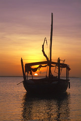 Zanzibar Sunset (djemde) Tags: ocean 2003 africa light sunset orange sun silhouette yellow tanzania boats fishing rocks indian zanzibar dhow smörgåsbord ricohrr120 kenwa