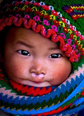 H'Mong babygirl - m mo nh (linh.ngan) Tags: travel winter portrait baby color reflection cute eye wool hat kids scarf children sweater rainbow vietnam traveling drslump runningnose hagiang minoritypeople dwcffchild