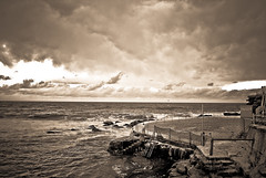 Bronte Baths ((reizen)) Tags: cloud sun beach sepia contrast fence waves antique sydney dramatic foam baths swimmer sliver process drama bronte lightroom froth cloudburst magicdonkey