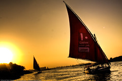 Felucca Sunset (KoRaYeM) Tags: trip cruise sunset orange sun grass yellow river ads advertising landscape geotagged boats boat flickr egypt sigma nile cairo hdr advertisment outing hdri lightroom waterscape maadi 2470 riverscape feluca photomatix supershot singleraw 40d mobinil feloka fuloka geo:lat=29960939 geo:lon=31237971