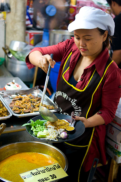 Jiap, a native of Phuket, serving up southern-style naam yaa, a fish curry over fresh rice noodles, from her stall at Bangkok's Or Tor Kor Market
