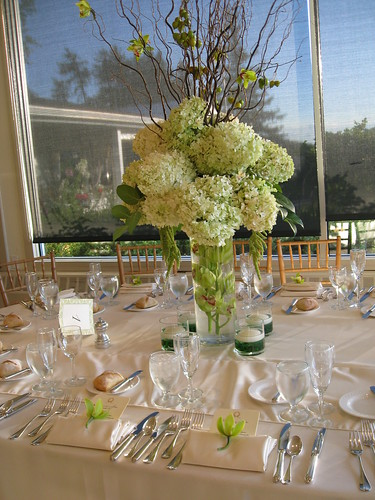 centerpiece - tall, wedding centerpiece. Flowers include PeeGee Hydrangea with green Cymdidium Orchids, wedding invitation, flowers, photos