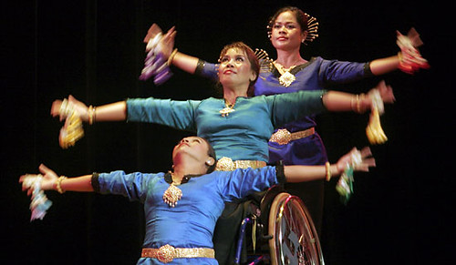 Three dancers, dressed in teal and purple, lined up in a row in performance. The front dancer is kneeling, the middle dancer is seated in a wheelchair, and the rear dancer is standing.