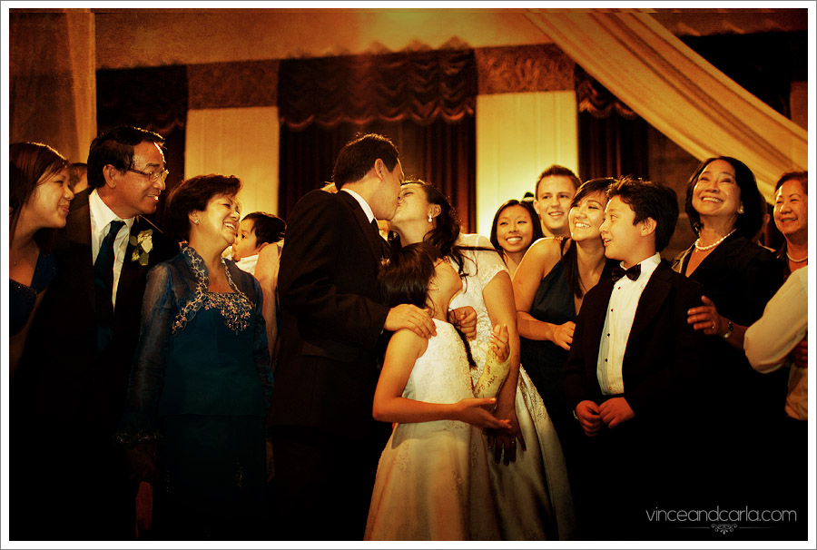 kiss with family looking