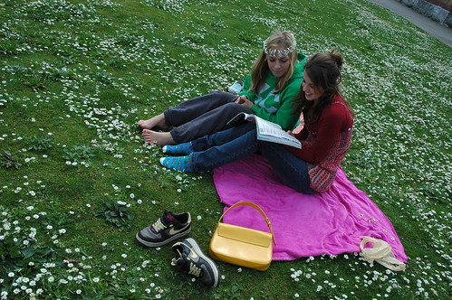 Girls reading a book in a field of daisies, one wears a daisey chain crown, Seattle, Washington, USA by Wonderlane