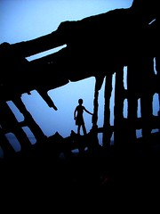 Sunken Pirate Ship (Casey Keith) Tags: boy beach silhouette boat pirateship