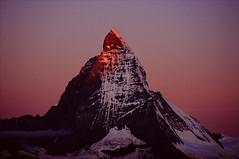 glowing peak (Ron Layters) Tags: pink red orange mountain sunrise geotagged dawn switzerland interestingness glow purple pentax earlymorning slide explore velvia transparency zermatt matterhorn fujichrome wallis alpenglow valais cervin pentaxmz10 cervino eastface mountainsalps elevation40004500m altitude4478m summitmatterhorn montcervin 4478m mattertal colouredsky ronlayters slidefilmthenscanned 14692ft geo:lat=45977639 geo:lon=7658844 highestpositioninexplore108onfridayfebruary132009