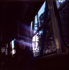 Tram Poltergeist (alistair dickinson) Tags: 120 6x6 film window girl  tram melbourne lensflare e6 stkildaroad hasselblad500cm pushed1stop fujichromeprovia100frdpiii carlzeissplanar80mmf28cft nomealice
