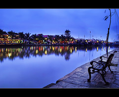i sat there...watching the world turn blue (explored) (PNike (Prashanth Naik)) Tags: world longexposure blue red sea sky orange reflection water colors yellow river lights boat town chair ancient nikon sitting seat an unesco vietnam hoian nightlight bluehour hoi d3000 worldheritagecenter pnike yahoo:yourpictures=reflections