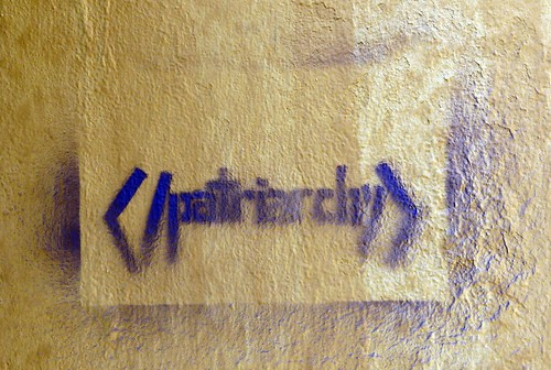 A graffiti in purple ink on a black wall, exhorting people to end patriarchy.