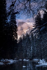 Half Dome Winter (Nick Carver Photography) Tags: california park travel trees winter sunset usa cloud mountain snow storm mountains reflection tree tourism nature water weather rock pine clouds reflections river relax landscape outdoors landscapes rocks branch framed branches stormy calm alpine valley rivers serenity frame western halfdome serene yosemitenationalpark wilderness sierranevada relaxed desolate yosemitevalley centralcalifornia mercedriver clearingstorm wildlifereserve natureparks ncpfineartprint nationalparksystem
