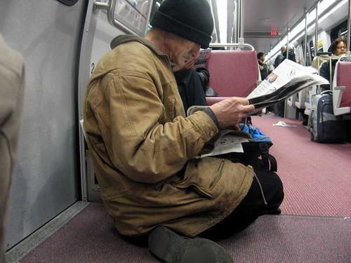 Man reading newspaper on Metro