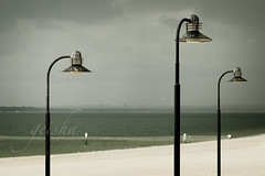 the mourners... (~ geisha ~) Tags: beach water grey sand streetlamps brightonlesands mourningthesun