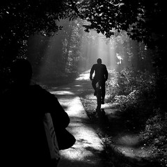 Lightbiking To Work (ElWanderer) Tags: uk light england blackandwhite bw monochrome bicycle silhouette blackwhite woking ray cyclist path surrey explore desaturation desaturated rays backlit shafts pathway shaft horsell interestingness10 explored i500 inexplore explore20081003