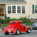 Plymouth Harbor: Old red hotrod car cruising down the strip